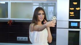 Una ragazza in un vestito bianco prende un selfie a casa in una cucina moderna stock footage