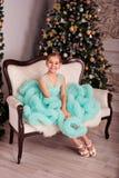 Una ragazza in un vestito blu fertile sta sedendosi sul sofà vicino all'albero di Natale fotografia stock libera da diritti