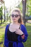 Una ragazza in un vestito blu sta sedendosi sulla natura fotografia stock libera da diritti