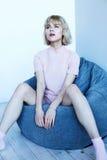 Una ragazza in un vestito domestico rosa vicino ad una sedia molle Belle pose del modello per la rivista di moda Immagine nei ton Immagine Stock Libera da Diritti