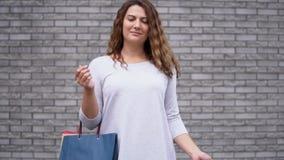 Una ragazza in un vestito leggero con i pacchetti dopo la compera con un umore buon sui precedenti di una parete delle pietre Mov archivi video