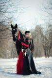 Una ragazza in un vestito nero lungo con un cavallo scuro immagine stock