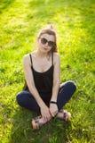 Una ragazza in un vestito nero sta sedendosi sull'erba verde fotografia stock libera da diritti