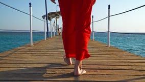 Una ragazza in un vestito rosso che cammina lungo un ponte vicino al Mar Rosso, Egitto video d archivio