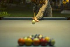 Una ragazza in un vestito a strisce tiene una stecca sopra un biliardo con il panno blu e le palle da biliardo vaghe fotografie stock