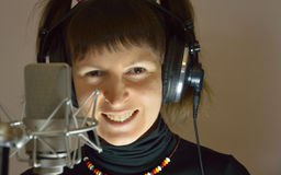 Una ragazza, una donna con le cuffie e un microp immagini stock