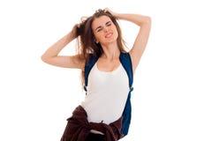 Una ragazza in una maglietta bianca con uno zaino sul vostro chiuso posteriore lei occhi e tiene vizioso i capelli delle mani Fotografie Stock Libere da Diritti