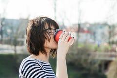 Una ragazza in una maglietta a strisce sta bevendo il caffè Immagini Stock Libere da Diritti