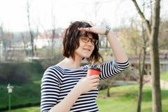 Una ragazza in una maglietta a strisce sta bevendo il caffè Fotografia Stock Libera da Diritti
