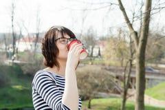 Una ragazza in una maglietta a strisce sta bevendo il caffè Fotografie Stock