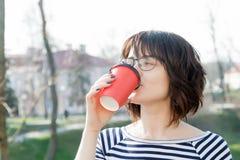 Una ragazza in una maglietta a strisce sta bevendo il caffè Fotografia Stock