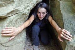Una ragazza in una piccola entrata della caverna Fotografia Stock