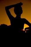 Una ragazza, una siluetta contro il tramonto luminoso Immagine Stock