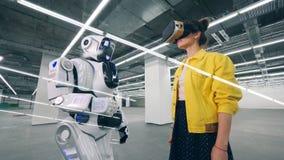 Una ragazza utilizza i vetri di VR in una stanza e tocca la mano dei droid archivi video