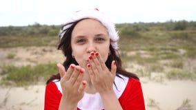 Una ragazza vestita come Santa Claus nel deserto Il concetto del viaggio per le feste del nuovo anno Buon anno e Buon Natale! stock footage