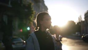Una ragazza in vetri alla moda mangia il gelato in un cono della cialda nei raggi del tramonto Abbigliamento casual camminare del stock footage