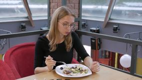 Una ragazza in vetri che si siedono in un caffè che mangia un'insalata di Caesar e che muove le sue spalle verso il battito della archivi video