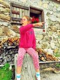 Una ragazza in vetri si siede su un ceppo vicino ad una parete di pietra fotografia stock