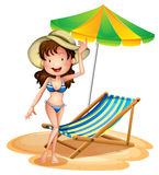 Una ragazza vicino ad un letto e ad un ombrello pieghevoli della spiaggia Immagine Stock