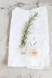 Una rama del romero con una inscripción caligráfica en un fondo blanco y concreto Imagen de archivo libre de regalías