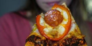 Una rebanada de pizza de salchichones, la cara borrosa de una muchacha en el fondo, primer imagenes de archivo