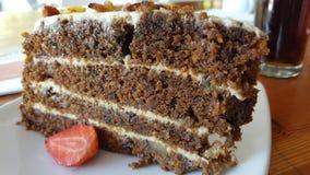 Una rebanada de torta de zanahoria deliciosa con el adorno de la fresa Foto de archivo