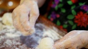 Una receta de la familia, manos del ` s de la abuela amasa la pasta para los bollos metrajes