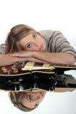 Una reclinación rubia linda sobre una guitarra. Fotografía de archivo libre de regalías