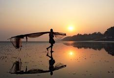 Una red de pesca del pescador que lleva en una playa del mar Fotos de archivo