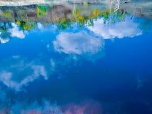 una reflexión del cielo azul con algunas nubes en la charca con algunas ondas imágenes de archivo libres de regalías