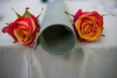 Una regolazione circolare rotolata della tavola del fazzoletto della tavola con le rose del orrange e di rosa fotografia stock
