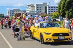 Una reina de belleza monta en un coche amarillo del mustango en el desfile de la Navidad de Rotorua imagenes de archivo