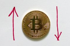 Una replica dorata del bitcoin su Libro Bianco scritto con la freccia rossa su e giù Concetto di finanza e di affari Fotografia Stock