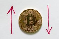 Una reproducción de oro del bitcoin en el Libro Blanco escrito con la flecha roja hacia arriba y hacia abajo Concepto del negocio Foto de archivo