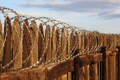 Una rete fissa di legno con barbwire Fotografie Stock