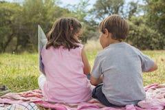 Una retrovisione di due bambini che si siedono su un asciugamano nell'erba Immagini Stock