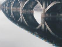 una riflessione di specchio del ponte nel fiume, Kyiv, autunno Fotografie Stock Libere da Diritti