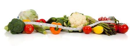 Una riga delle verdure e una misura di nastro su bianco fotografie stock libere da diritti