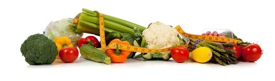 Una riga delle verdure e una misura di nastro su bianco fotografia stock