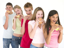 Una riga di cinque amici che mangiano gli hamburger Fotografie Stock