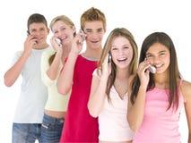 Una riga di cinque amici sul sorridere dei telefoni cellulari Fotografia Stock Libera da Diritti