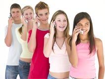 Una riga di cinque amici sul sorridere dei telefoni cellulari Immagini Stock Libere da Diritti
