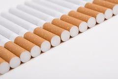 Una riga di sigarette sul bianco Immagine Stock