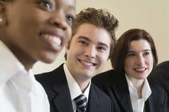 Una riga di tre genti di affari sorridenti alla riunione. Fotografie Stock