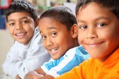Una riga di tre giovani ragazzi di banco sorridenti nel codice categoria Immagine Stock