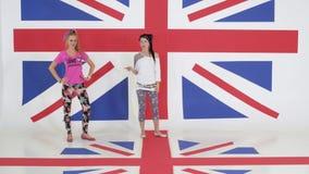 Una ripetizione di due femmine carismatiche che ballano sul fondo della bandiera di britannici stock footage