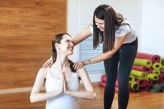 Una risata di due giovani donne Donna incinta che si esercita, aiuto dell'istruttore Fotografie Stock