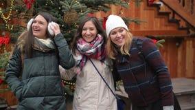 Una riunione felice di tre amici che abbracciano nel mercato di Cristmas, amiche di risata divertendosi nel mercato di natale archivi video