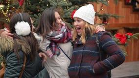 Una riunione felice di tre amici che abbracciano nel mercato di Cristmas, amiche di risata divertendosi nel mercato di natale stock footage
