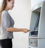 Una riuscita giovane donna che ritira felicemente soldi dal suo libretto di risparmio immagini stock